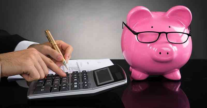 Close-up Of Businessperson With Piggybank Calculating Tax At Desk